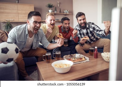 Group of friends watching soccer game on television, celebrating goal.