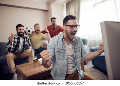 Group of friends watching soccer game on television ,celebrating goal and screaming.