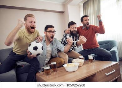Group of friends watching soccer game on television, celebrating goal together.