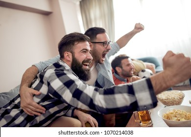 Group of friends watching soccer game on television and celebrating goal.