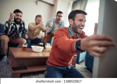 Group of friends watching soccer game on television, celebrating goal at home.