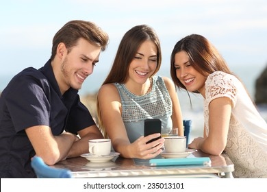 Group of friends watching social media in a smart phone in a restaurant with the beach in the background