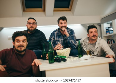 Group of friends watching sport on TV at home