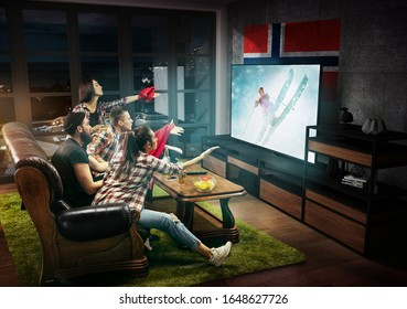 Group of friends watching TV, match, championship, sport games. Emotional men and women cheering for favourite team of skiing in Norway with flag. Concept of friendship, sport, competition, emotions.