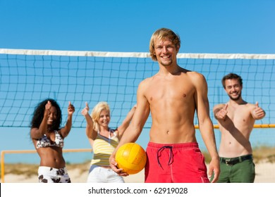 Group of friends - women and men - playing beach volleyball, one in front having the ball