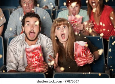 Group of frightened people watching movie spill popcorn