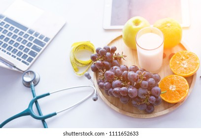 group of fruits slice orange, grape, apple and glass of milk on table with laptop, tablet and stethoscope background. The object of healthy food and drink for breakfast health care concept.