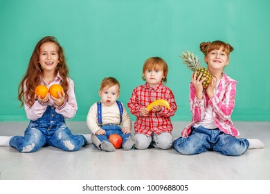 A group of fun children are playing in the room. Useful Fruits. The concept of a healthy lifestyle, food, childhood, vitamins, vegetarianism.