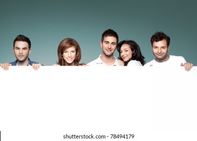 group of funny friends holding a blank banner