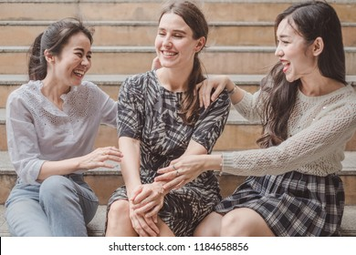 Group of funny girl friends meeting up, sitting at some place, smiling and laughing, ideas for vacation, holiday, lifestyle, meeting, best friends and great time concept.