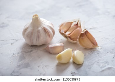 Group of garlic cloves scattered on a table on a white background. An important ingredient in different cuisines of the world. A healthy product.