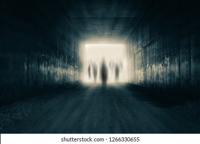 A group of ghostly figures emerging from the light at the end of a dark sinister tunnel. With a high contrast edit.