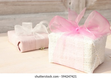 Group of gift boxes wrapped with textured linen cloth and decorated with beautiful festive bow. Amazing contrast of white and pink color. Great idea for girls presents geving. Full light composition