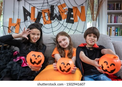 Group of girl and boy kids dress up costume and hold the pumpkin bowl for trick or treat for Halloween day theme coming soon together