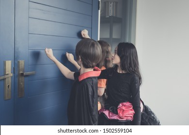 Group of girl and boy kids smiling and dress up as Halloween vampire costume and knock on door for trick or treat for Halloween night day theme coming soon together