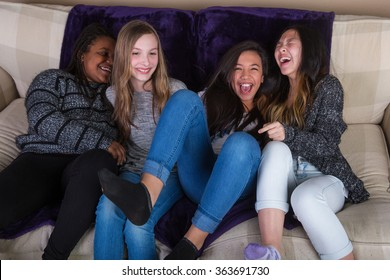 Group of girl friends laughing and having fun at home