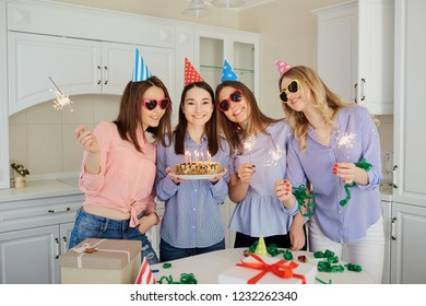 A group of girlfriends with a cake with candles celebrate a birt