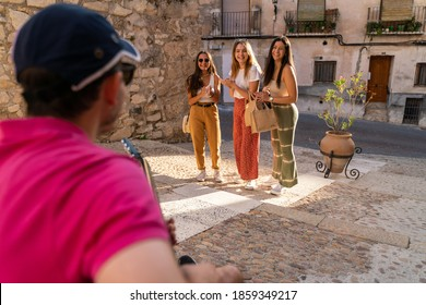 Group of girlfriends looking at a busker playing the guitar on the streets while doing tourism