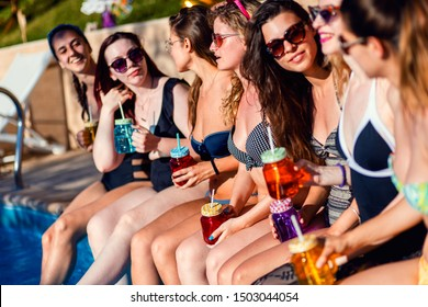 Group of girlfriends at a poolside summer party sitting at the edge of a swimming pool drinking and having fun.