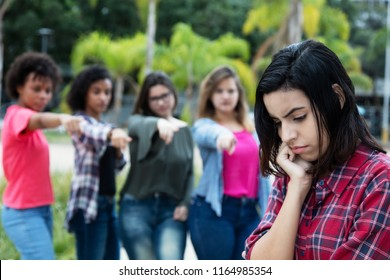 Group of girls bullying an arabic young adult woman without friends outdoors