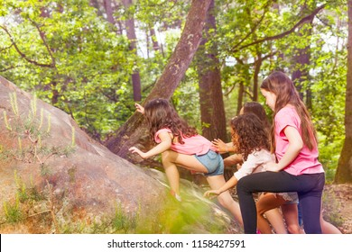 Group of girls climb on the rock in forest