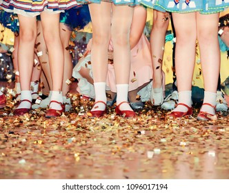 Group of girls in colorful dresses standing on stage