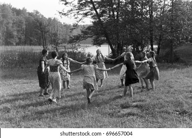 Group of girls dancing in circle on grass in front of lake
