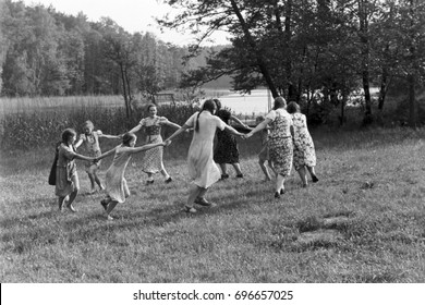 Group of girls dancing in circle on grass
