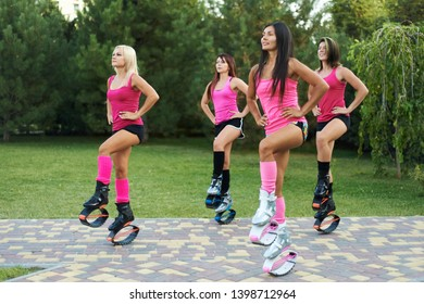group of girls doing exercises in kangoo jumping boots. outdoor fitness workout in team