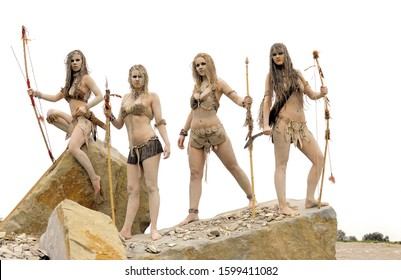 A group of  girls dress up as neanderthal women. They are  armed with spears, knives and bow and arrows. Covered with  mud, filth and dirt they are seen in a stone quarry surrounding.