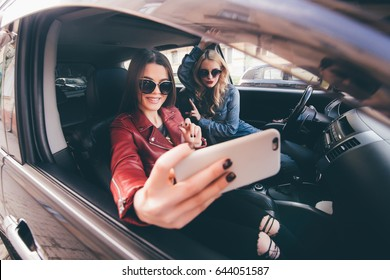 Group of girls having fun with the car. Taking selfie while driving