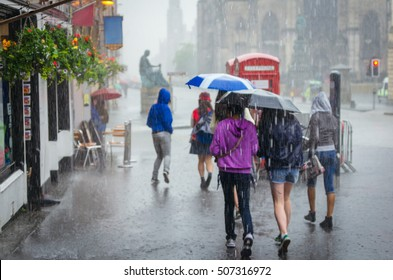 Group of girls hurry at the rain with umbrella in the city
