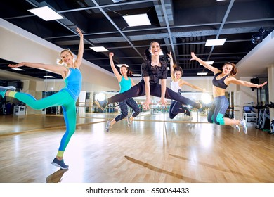 A group of girls jump with smiles in the gym