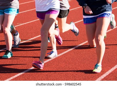 A group of girls on a cross country team does speed training on a red track while wearing spikes
