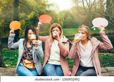 group of girls in the park drinking beer together while holding a thought bubble on their hands. Friendship and communication concept.