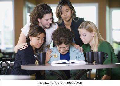 Group Of Girls Praying For Senior Woman