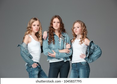 The group of girls standing together and posing at camera. Studio portrait of young attractive fashion caucasian teen girls dressed in jeans grouped together. Front view over gray studio. Kids fashion