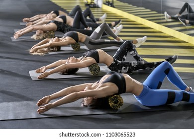 Group of girls is training with black-yellow foam rollers on the gray mats in the gym. They are wearing the multicolored sportswear: pants, tops and sneakers. Horizontal.