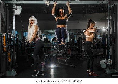 Group of girls is training with TRX straps and upper block parallel grip toi the chest in the gym. They are wearing the sportswear. Horizontal.