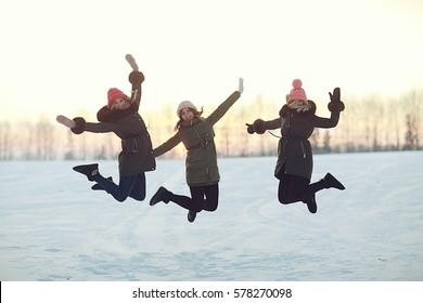 group of girls winter nature fun jump