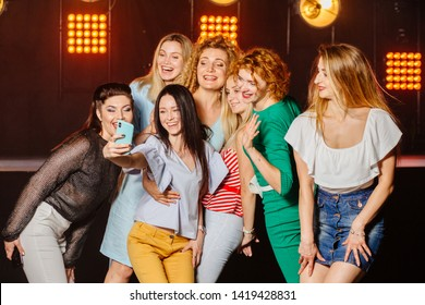 Group glamorous female friends making selfie with smartphone during holidays party relaxing celebrating dancing at party in night club together. Seven women partying in a nightclub make selfie photo