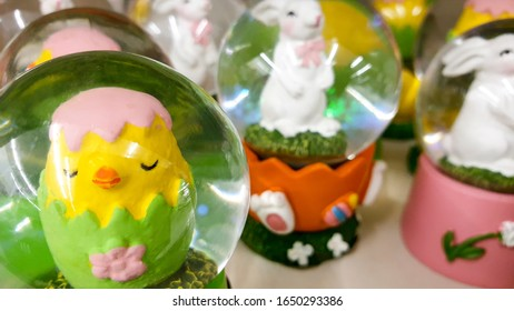 A group of glass globes filled with Easter animals, traditional Easter decorations to ornate the home, selective focus on foreground.
