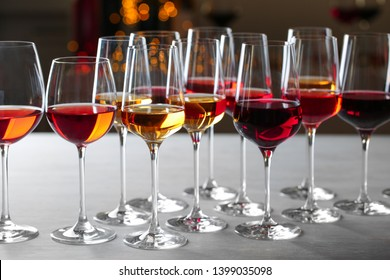 Group of glasses with different wines on table against blurred background