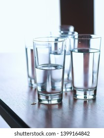 Group of glasses on table filled with still mineral water