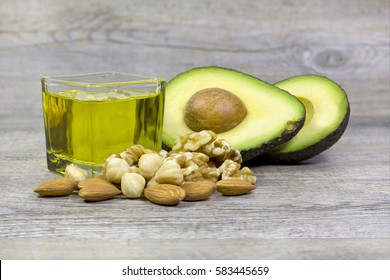 Group of good fats food examples (olive oil, dry fruits and avocado) on a wooden surface.