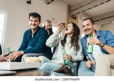 Group of good friends at home party. Eating pizza from delivery box, pop corn, drinking, playing fool and enjoying holidays together