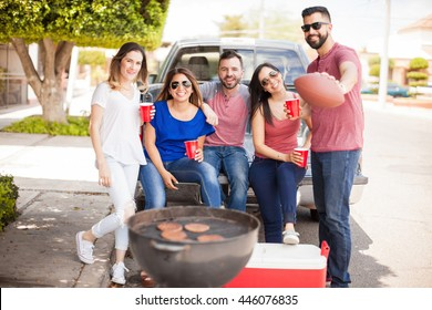 Group of good looking friends and football fans grilling hamburgers and drinking beer while tailgating at a sunday game