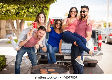 Group of good looking Hispanic friends drinking beer and having some fun together at a barbecue