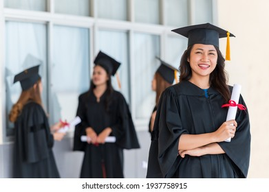 group of graduates Asian student in academic gown and graduation cap holding diploma