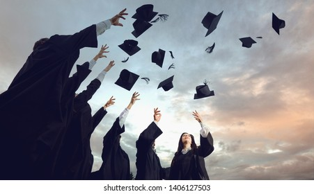 A group of graduates throws hats up into the sky.